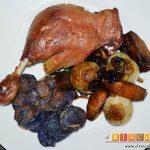 Confit de pato con cebollitas francesas, manzanas, pasas y piñones caramelizados y papas azules chips