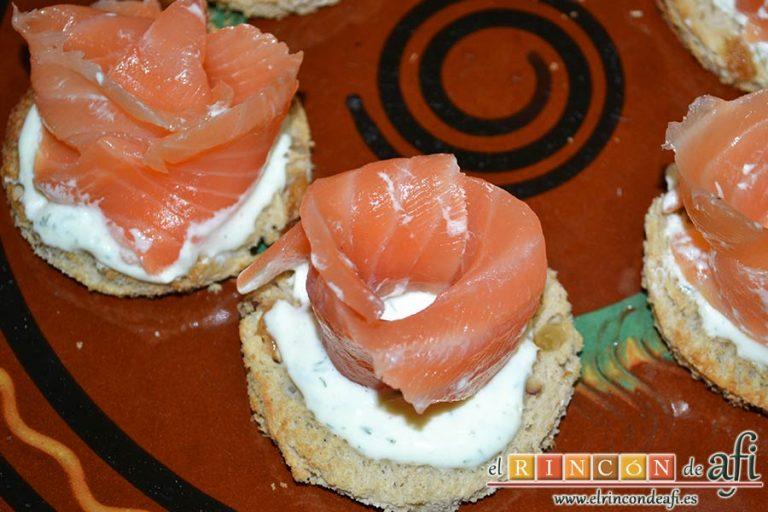 Rosas de salmón, poner una cucharada de crema sobre cada círculo y formar una rosa con salmón enrollando una loncha
