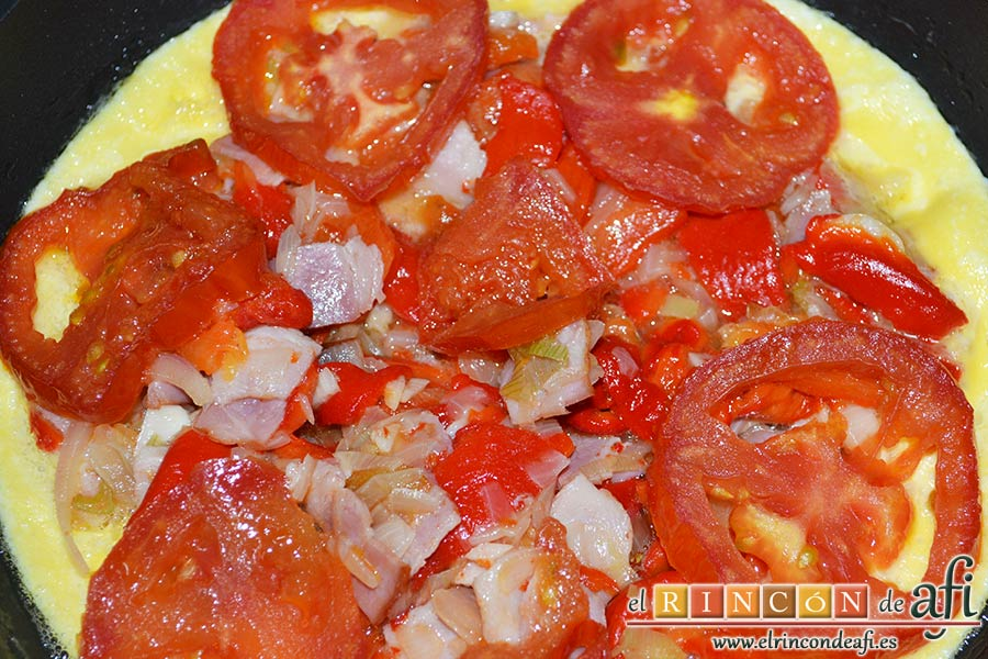 Frittata de pimientos, bacon y queso, poner encima las rodajas de tomate sofritas