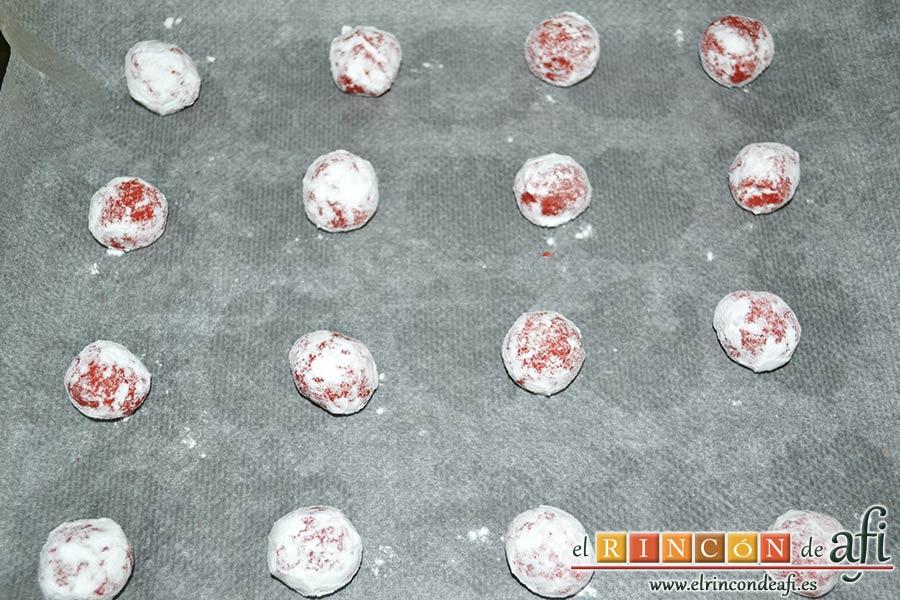 Red Velvet Cookies, rebozar las bolitas en azúcar glass y colocarlas sobre una bandeja de horno