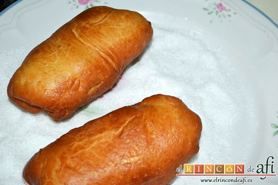 Xuxos rellenos de crema pastelera, una vez fríos pasarlos a un plato con azúcar blanquilla