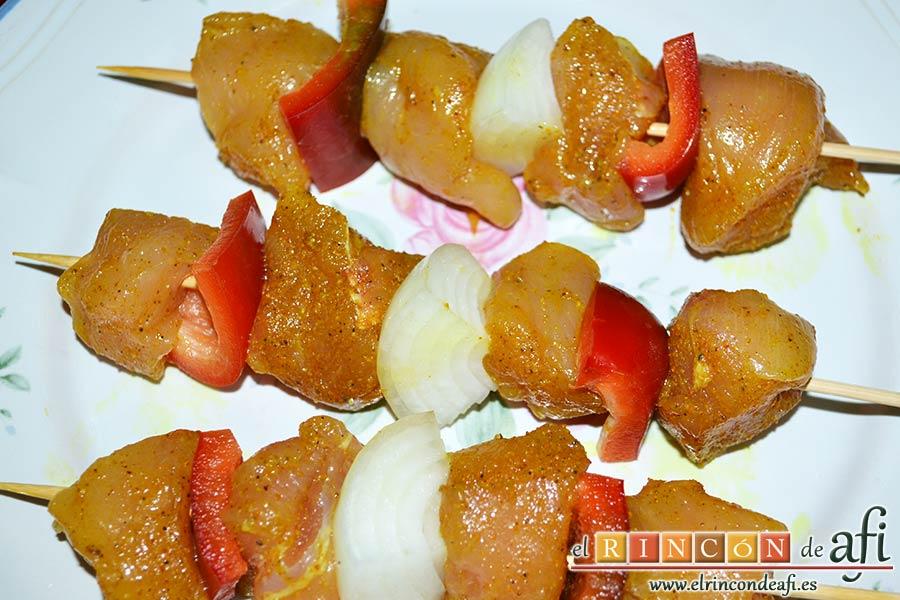 Brochetas de pechuga de pollo marinadas al curry con cebollas y pimientos, insertar en las brochetas alternando ingredientes