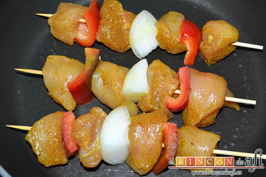 Brochetas de pechuga de pollo marinadas al curry con cebollas y pimientos, dorar sin nada de aceite