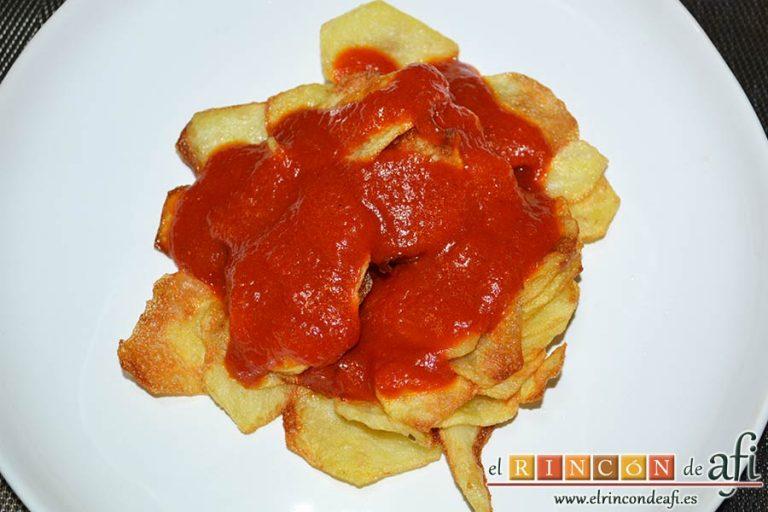 Presa ibérica adobada con papas al pelotón, hacer una cama de papas, poner por encima el tomate frito