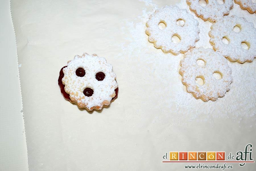 Galletas con masa quebrada y mermelada de frambuesas, cubrirla con una de las galletas agujereadas y cubiertas de azúcar glass