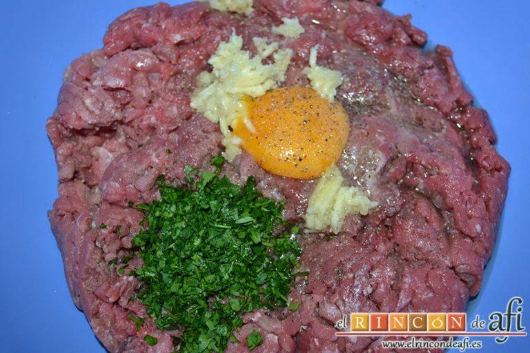 Albóndigas con salsa de cebollas, en un bol amplio colocamos las carnes picadas y le añadimos el huevo, los dientes de ajo machacados, la sal y la pimienta, y el manojito de perejil fresco picado
