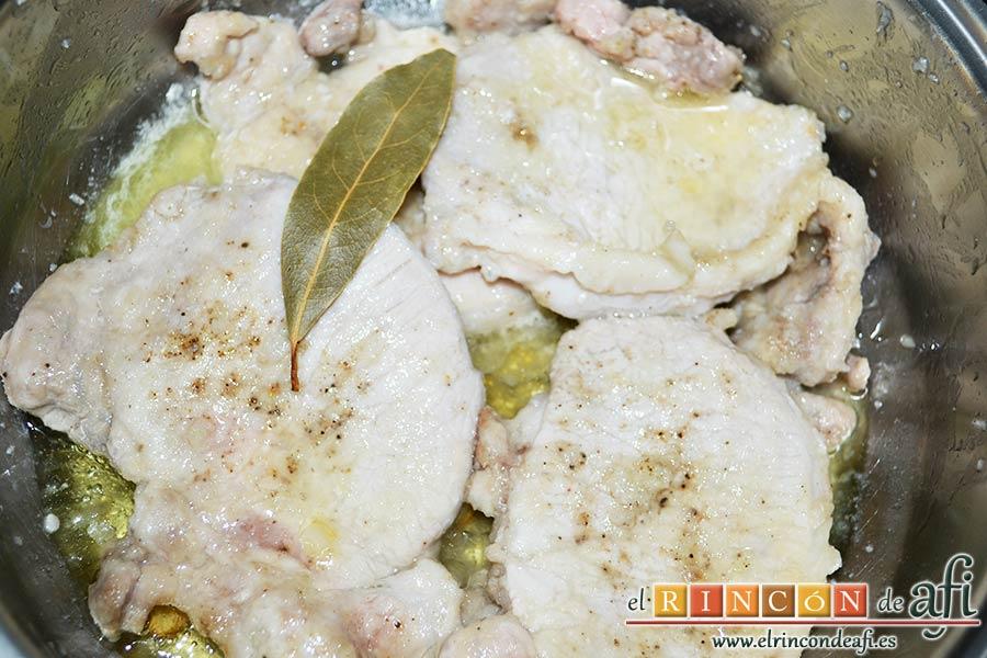 Chuletas de cerdo con alcaparras y anchoas, añadir el zumo de limón y una hoja de laurel