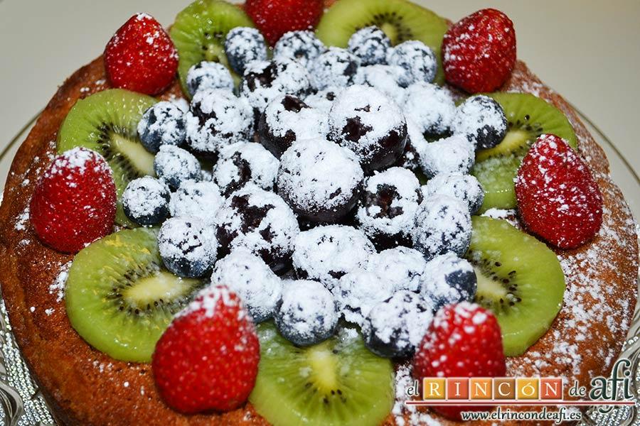 Pastel alemán con frutos rojos y kiwi, espolvorear la fruta con azúcar glass
