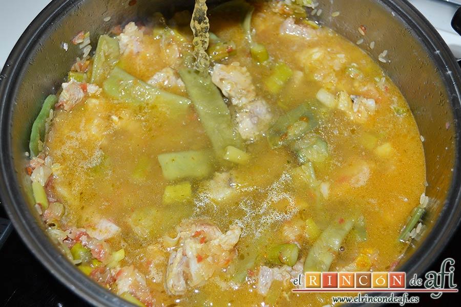 Arroz con costilla de ternera blanca, judías verdes, ajos tiernos y espárragos trigueros, dar unas vueltas y añadir el caldo de verduras