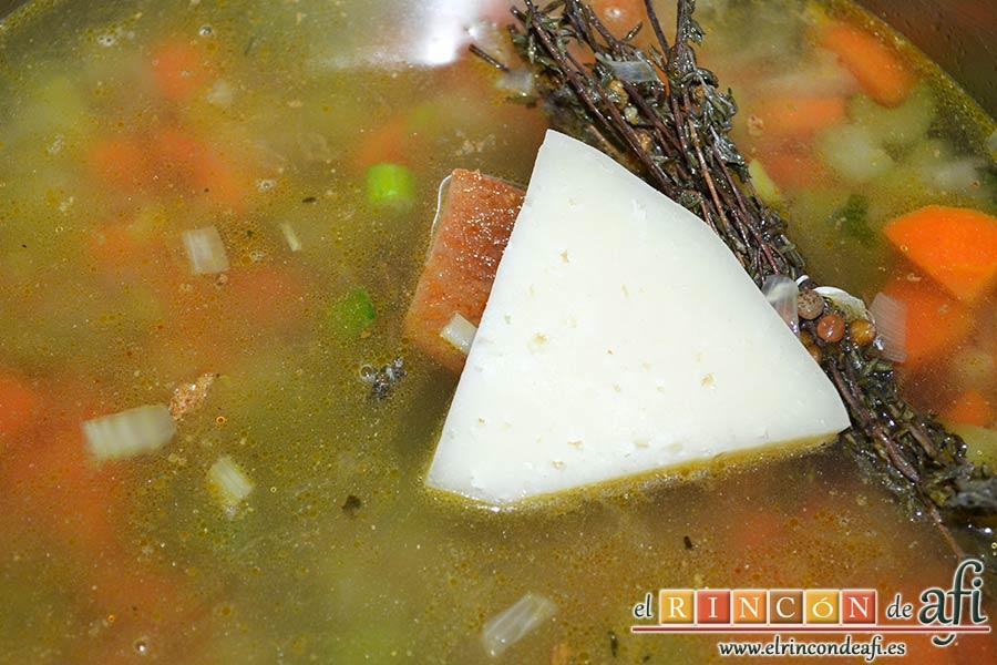 Pasta rota con lentejas, verter caldo hasta cubrir y el trozo de queso