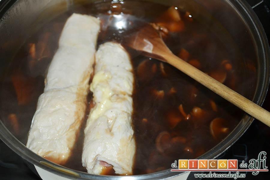 Rollitos de pechuga de pollo con salsa de setas variadas y reducción al Pedro Ximénez, introducir los rollos en el cazo con la salsa