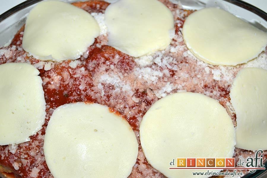 Berenjenas a la parmesana, espolvorear con queso parmesano y lonchas de mozzarella