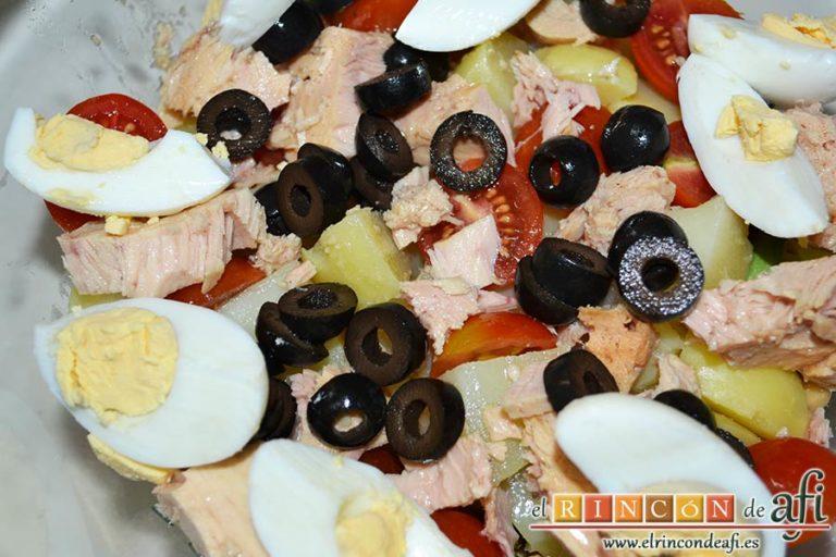 Ensalada de garbanzos, papas, tomates, atún y huevos, añadir los huevos pelados y partidos en cuartos, así como las rodajas de aceituna