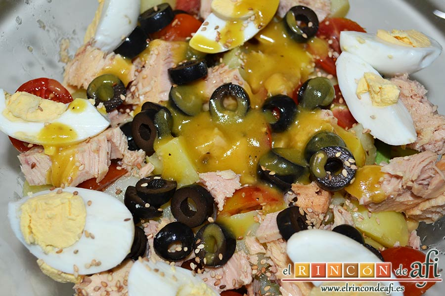 Ensalada de garbanzos, papas, tomates, atún y huevos, aliñar