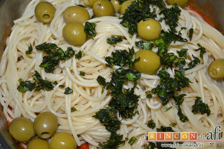 Espaguetis con salchichas y aceitunas, añadir la albahaca fresca picada y remover