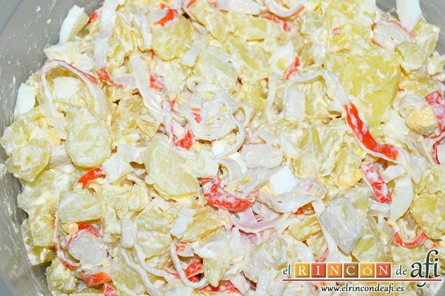 Ensalada de palitos de cangrejo, piña y papas, añadir la mayonesa y mezclar