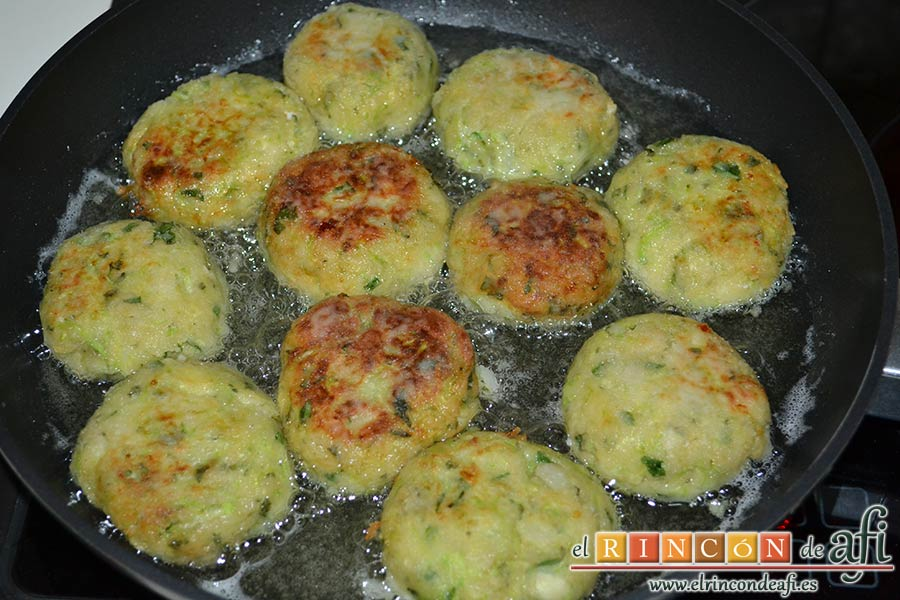 Keftedes de calabacín con queso feta y salsa tzatziki, darles la vuelta para hacerlas por ambos lados