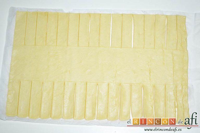 Trenza de hojaldre con bacon y queso, dividir el hojaldre en tres rectángulos y cortarlo en tiras como en la foto