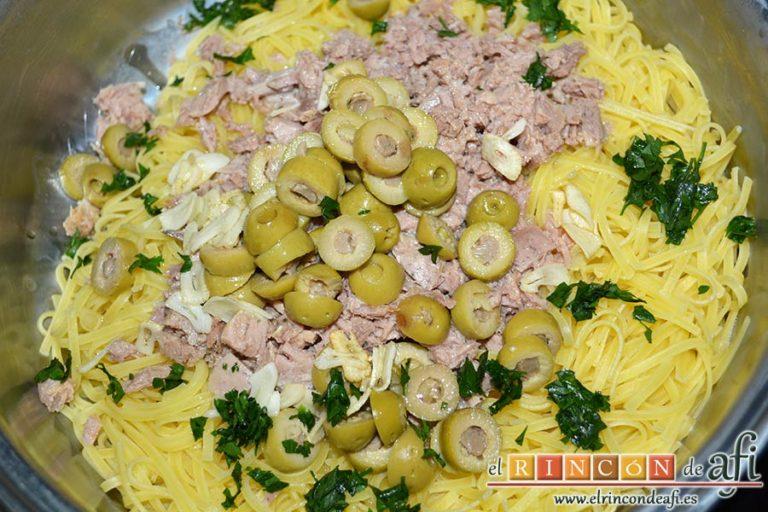Espaguetis con atún y aceitunas, verter por encima el aceite con los ajos y el perejil picado