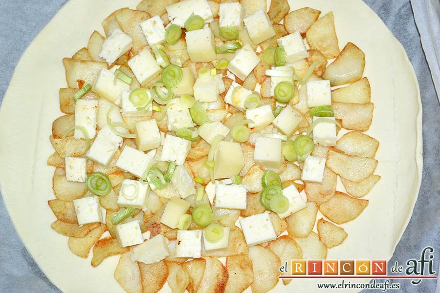 Tarta hojaldrada de papas con queso semicurado y lacón, añadir las cebolletas