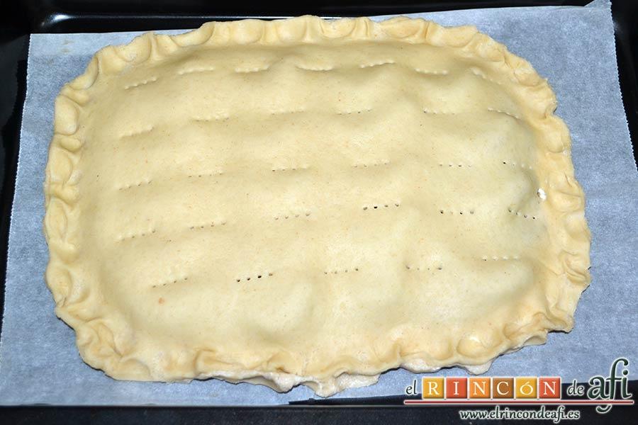 Empanada de langostinos y cebolla caramelizada, sellar los bordes con repulgue y pinchar la masa con un tenedor