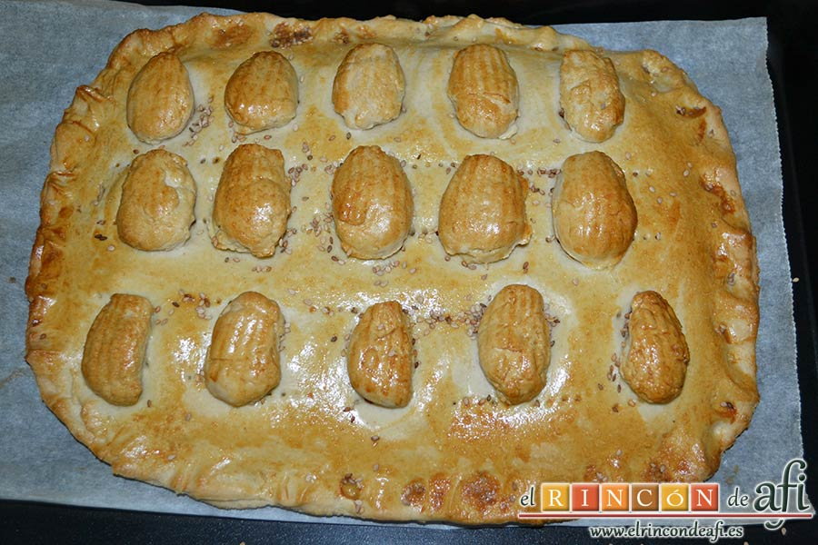 Empanada de langostinos y cebolla caramelizada, espolvorear con semillas de sésamo y hornear