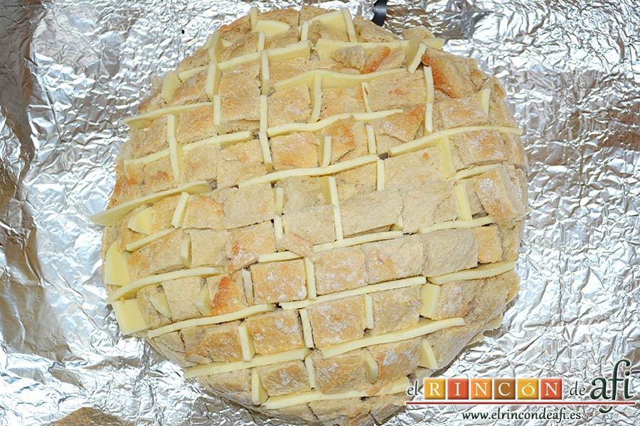 Pan erizo con queso y aceite de tomate y ajo, poner el pan sobre papel de aluminio en una bandeja de horno