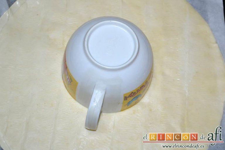 Roscón de hojaldre para Reyes, desplegar las láminas de hojaldre, pegarlas con agua de azahar y poner una taza en el centro