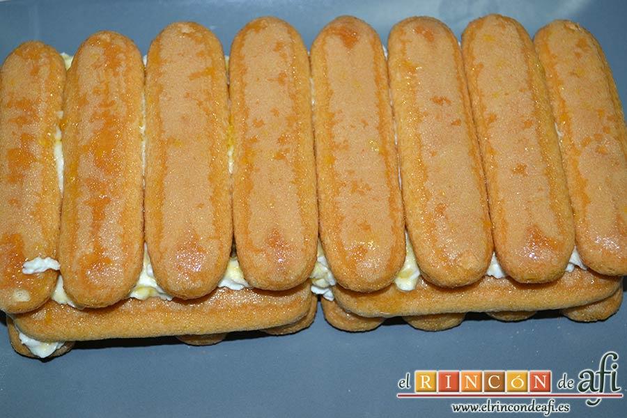 Tiramisú de frambuesas con almíbar de naranja, concluir con una última capa de crema y bizcochos